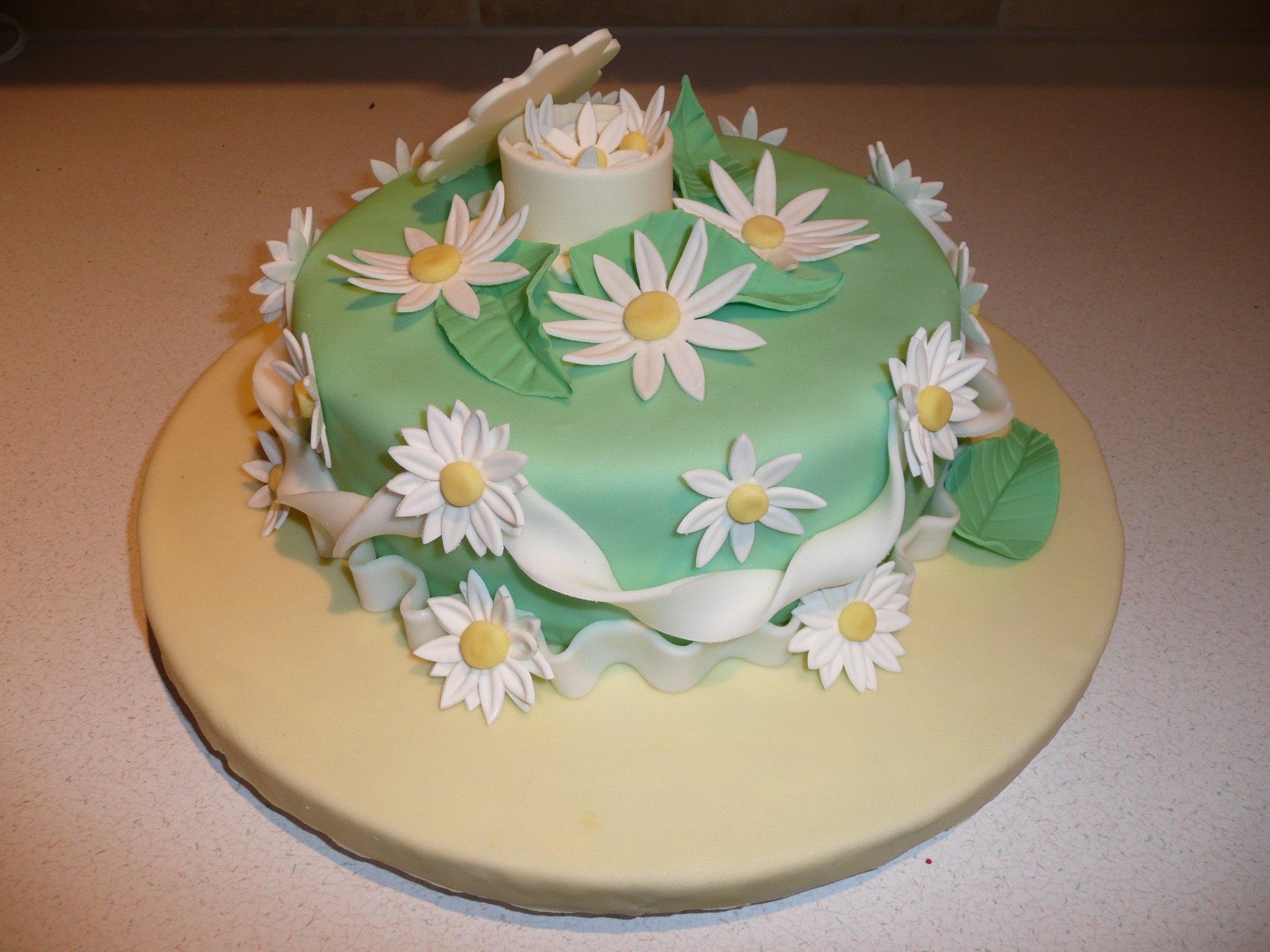 It is an 8 inch round cake covered in green fondant. The board is also covered in yellow fondant. I made daisies ...