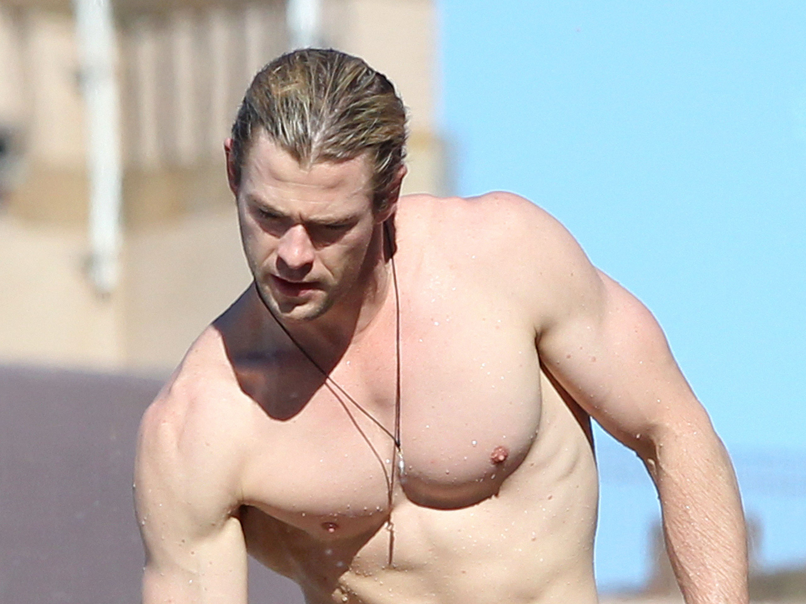 Chris Hemsworth shows off his ripped body as he chills by his hotel pool.