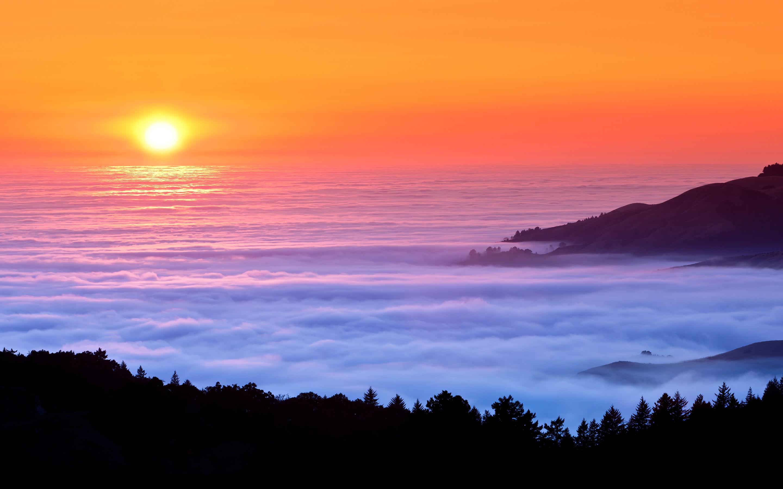 Sunset fog over sea mountains
