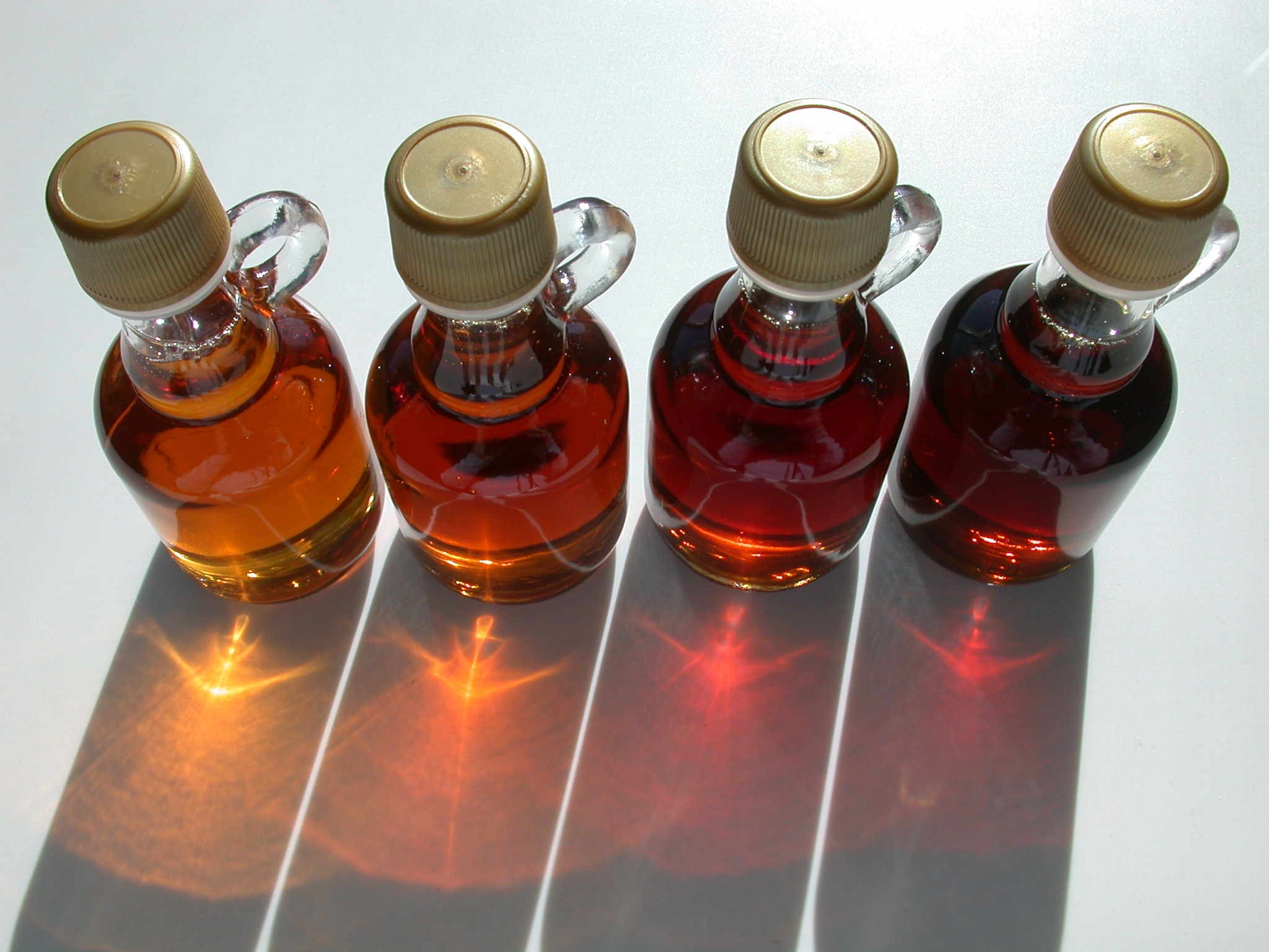 "Old US maple syrup grades, left to right: Grade A Light Amber (""Fancy""), Grade A Medium Amber, Grade A Dark Amber, ..."