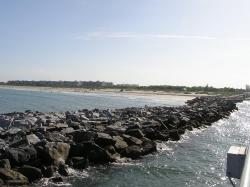 Looking back at Jetty Park Beach from the fishing pier. The rocks in the foreground are the jetty that protects the beach from erosion.