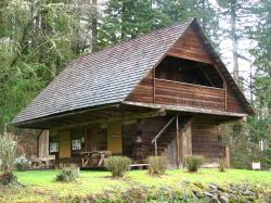Photograph of a two-story log cabin, with an extreme overhang of the second