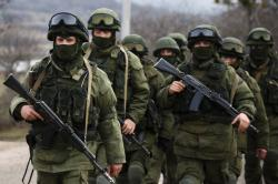 Armed men, believed to be Russian servicemen, march outside a Ukrainian military base near the Crimean city of Simferopol.Photo: Reuters