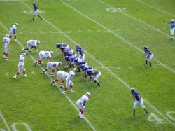 Players assemble at the line of scrimmage in an American football game.