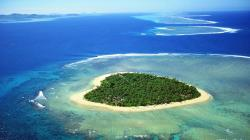 This is the island of Tavarua in Fiji, five miles by boat from the main island of Viti Levu. It is 29 acres in size and surrounded by a coral reef.