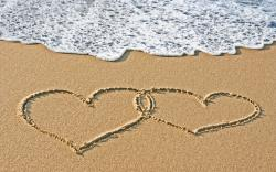 Sand hearts couple at the beach
