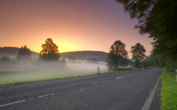 Sunrise road morning mist