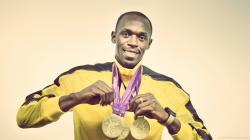 Usain Bolt holds three golden medals picture