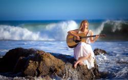 Woman playing guitar coast